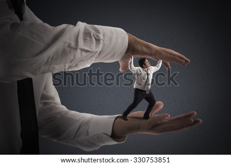 Big hands that crush a small man - stock photo