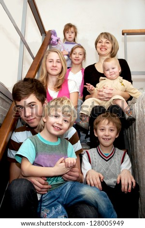 Big happy family - a mother and many children sitting on the stairs at home. Family concept. - stock photo