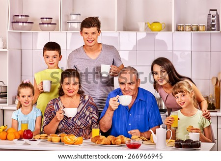 Big happy family have breakfast at kitchen. Three generations. - stock photo