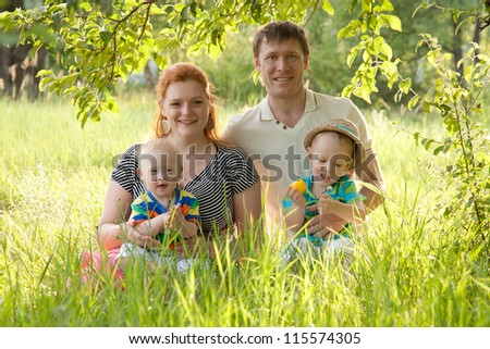 Big happy family - mother, father and children sitting in the grass under a tree in the park. One of the kids - with Down syndrome. Summer holiday. - stock photo