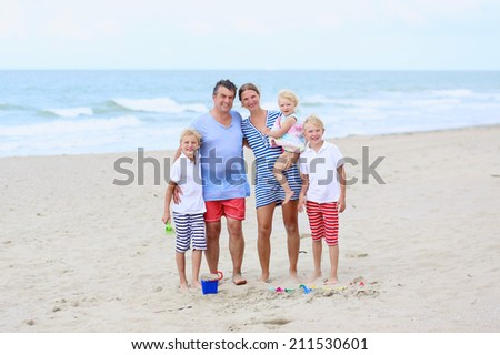 Big happy family of five - young active parents with three kids, twin teenager sons and cute toddler daughter - enjoying summer vacation together on the beach at the sea - stock photo