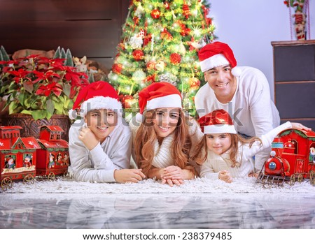 Big happy family wearing Santa hat, celebrating Xmas at home near beautiful decorated Christmas  tree, spending winter holidays together concept - stock photo