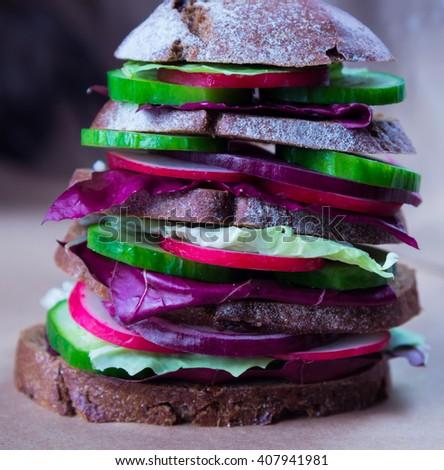 Big healthy fast food vegan sandwich with fresh vegetables - stock photo