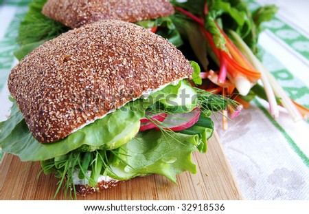 Big healthy rye bread sandwich with fresh with radish, cucumber, green vegetables and herbs on a wooden kitchen board, blur background - stock photo