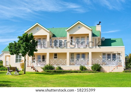 Big house - front view, grass, bench, tree. Shot in Kuils River, near Stellenbosch/Cape Town, Western Cape, South Africa. - stock photo