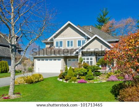 Big house with triple garage doors and nicely landscaped front yard. North America. - stock photo