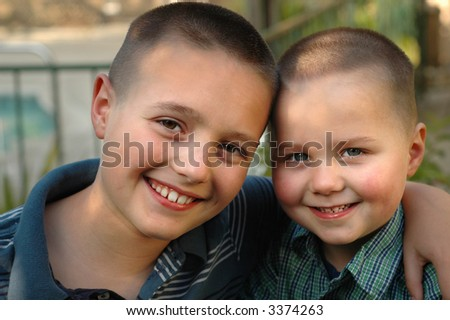 Big hug between two little brothers standing in their backyard - stock photo