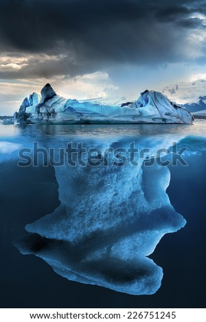 Big iceberg underwater with a small part floating - stock photo