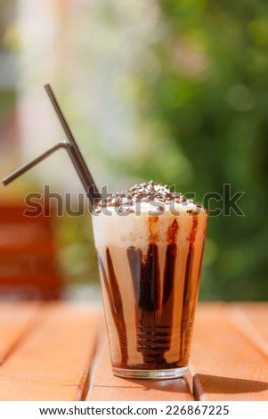 Big iced coffee with whipping cream and chocolate sprinkles on top, outdoors - stock photo