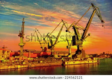 Big industrial cranes on a sunset sky background. - stock photo
