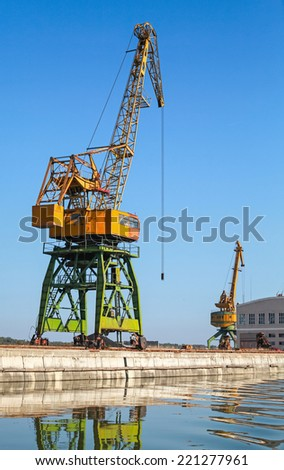 Big industrial harbor cranes works on the river coast in Bulgarian port
