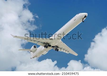 big jet plane landing on blue cloudy sky background - stock photo
