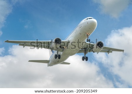 big jet plane taking off on blue cloudy sky background - stock photo