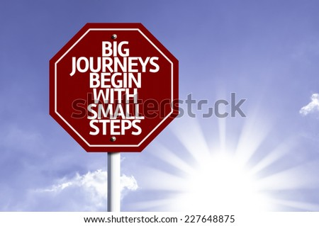 Big Journeys Begin With Small Steps written on red road sign with a sky on background - stock photo
