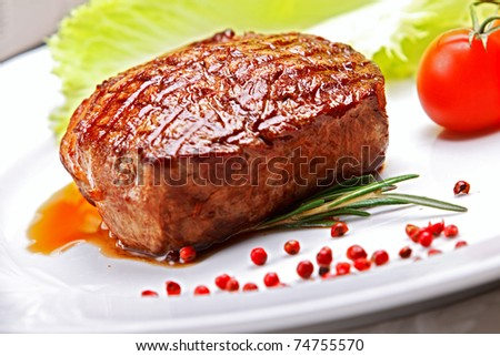 Big juicy grilled steak with greens on the plate