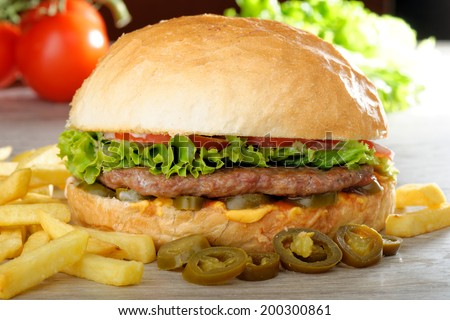Big juicy Mexican burger with spicy jalapenos, nacho cheese and a chips - stock photo