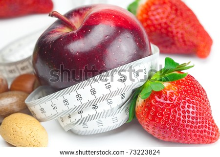 big juicy red ripe strawberries,apple,nuts and measure tape isolated on white - stock photo