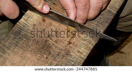 Big knife cutting the tip of a Cuban cigar on a plank. - stock photo