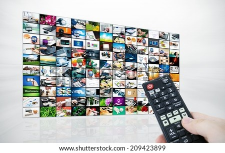 Big LCD panel with television stream images and remote control in hand - stock photo