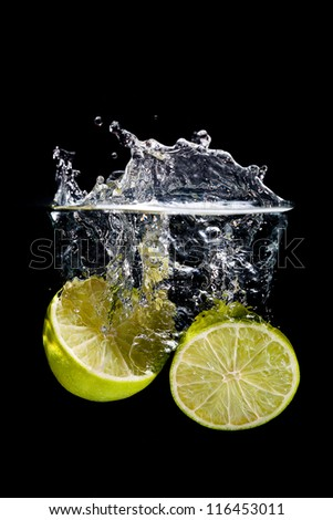 Big lemon splashing into the water on black background - stock photo