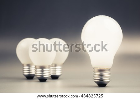 Big light bulb glowing with group of small light bulbs on background, leader, differentiation concept - stock photo