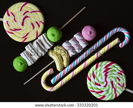 Big lolipops, candy canes and marshmallow on black background - stock photo