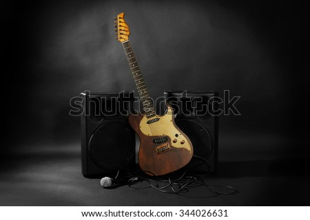 Big loudspeakers with electric guitar and microphone on black background - stock photo
