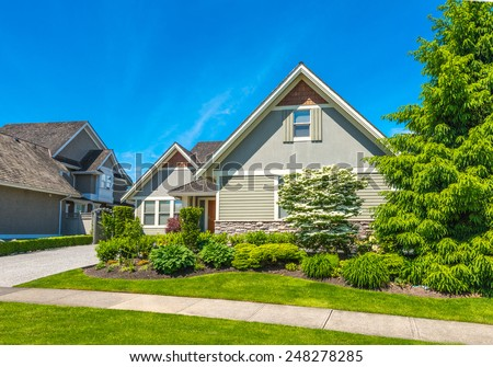 Big luxury custom made house with nicely landscaped front yard and driveway to garage in the suburb of Vancouver, Canada. - stock photo