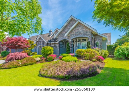Big luxury custom made house with nicely landscaped front yard in the suburb of Vancouver, Canada. - stock photo