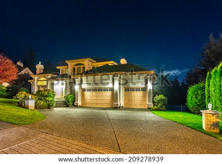 Big luxury house with double doors garage at night, disk, sunset, sunrise time in suburbs of Vancouver, Canada. - stock photo