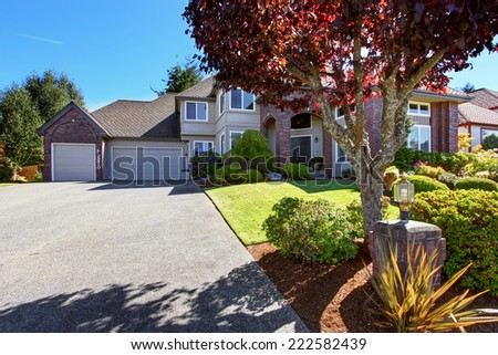 Big luxury house with tile roof and brick trim. View of garage with driveway. Beautiful front yard landscape - stock photo