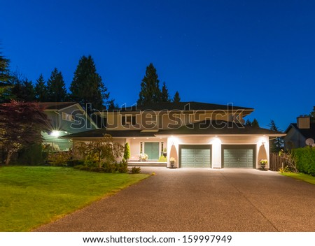 Big luxury house with two garages and long nicely paved driveway at dusk, night time in suburbs of Vancouver, Canada. - stock photo