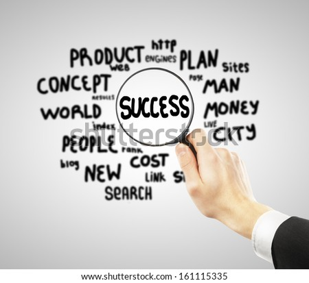 big magnifier in hand looking at success - stock photo