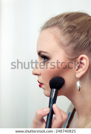 Big Make up brush. Beauty Woman. Makeup applying. Beautiful fashion model girl face closeup. - stock photo