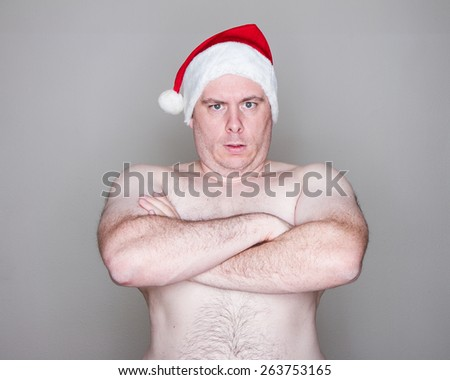 Big man being topless with a santa hat on - stock photo