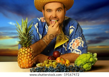 big man eating fruit by the beach - stock photo
