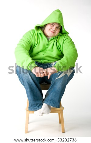 Big man in a green jacket with hood sitting on a chiar - stock photo
