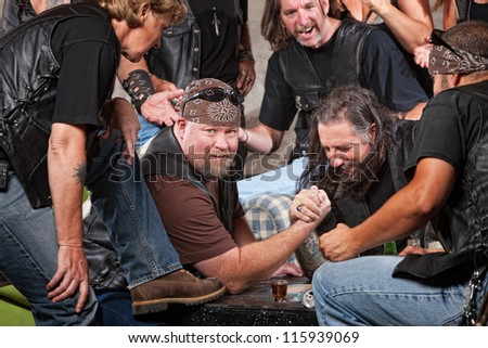 Big man in biker gang losing arm wrestling match