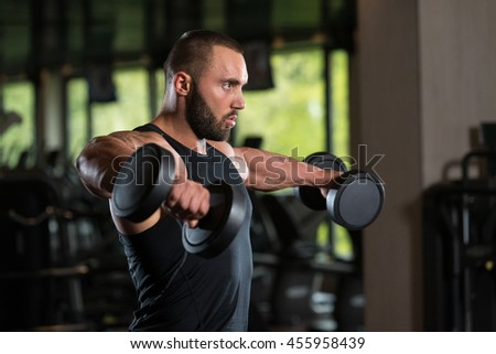 Big Man Standing Strong In The Gym And Exercising Shoulders With Dumbbells - Muscular Athletic Bodybuilder Model Exercise In Fitness Center - stock photo