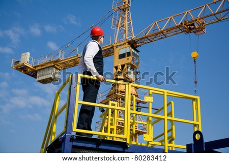 Big Manager, architect and supervisor oversees work on the construction site. In the background is a large crane. Selective focus, best focus is on the head Manager - stock photo