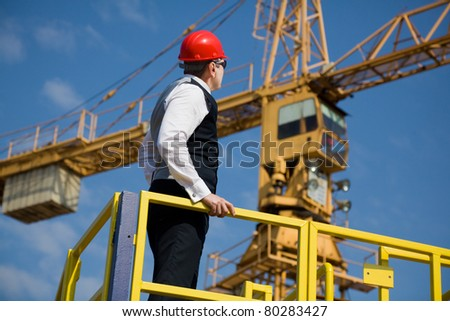 Big Manager, architect and supervisor oversees work on the construction site. In the background is a large crane. Selective focus, best focus is on the head Manager