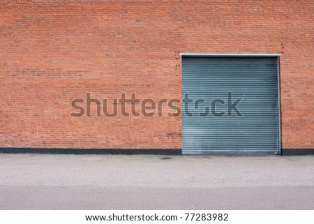 Big metal garage door on big brick wall.