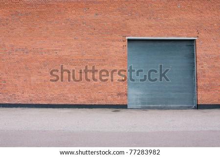 Big metal garage door on big brick wall. - stock photo