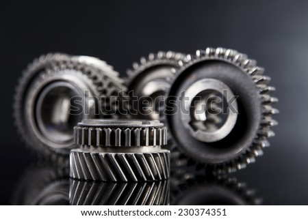 Big metal gears on glossy black background - stock photo