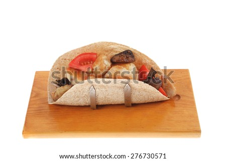 big mexican taco with tomatoes and mushroom on wood plate isolated over white background - stock photo