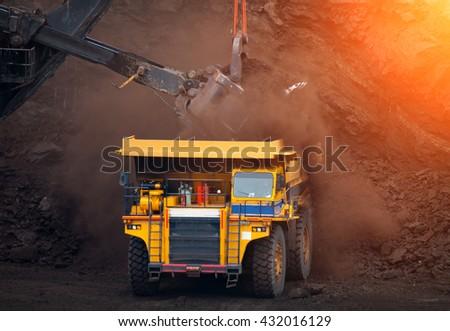 Big mining truck unload coal in coal mining, mining production, mining industrial, mining process, mining truck - stock photo