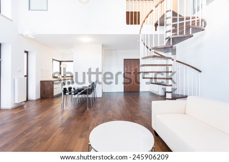 Big modern lounge with wooden spiral stairs - stock photo