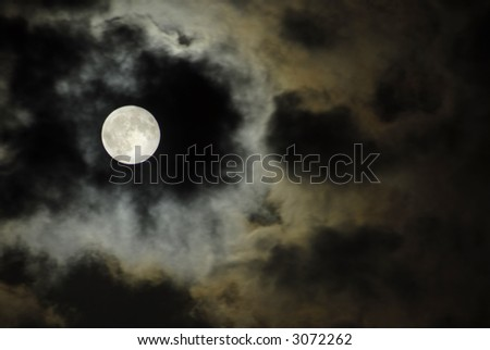 big moon over the clouds in a dark night