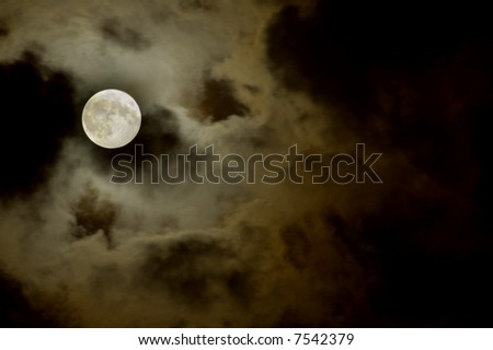 big moon over the clouds in a dark night - stock photo