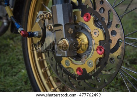 Big motorbike disc brake with new condition on a green spring grass background.